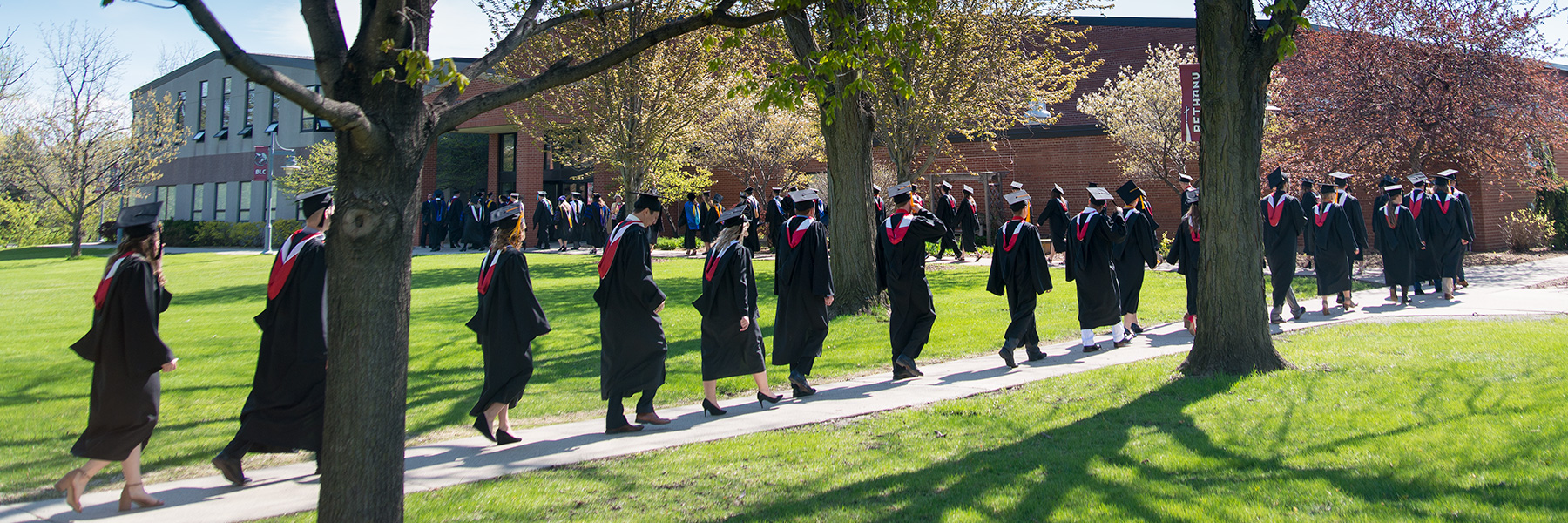 students walking on a sidewalk in graduation robes and caps