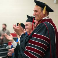 Bethany President Gene Pfeifer clapping at a commencement ceremony