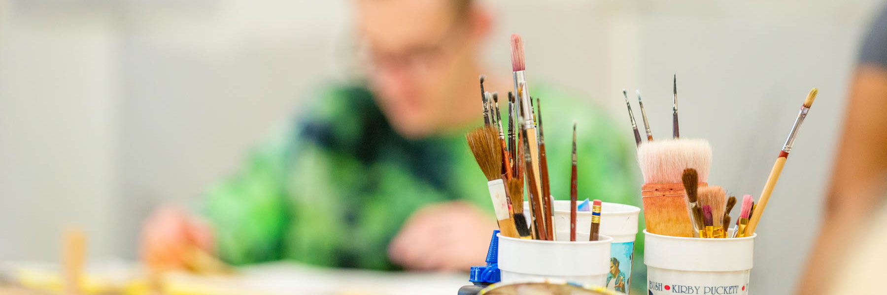 various sizes of paint brushes are sitting in cups while a blurred our student works in the background
