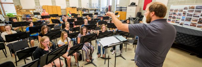 band director stands and conducts a rehearsal of students seated behind music stands while playing instruments
