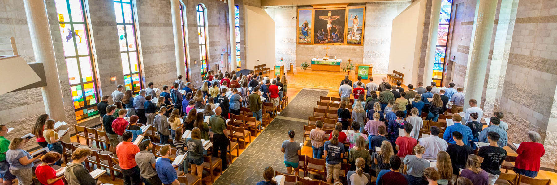 students, faculty, and staff standing in rows of chairs during a chapel service in trinity chapel