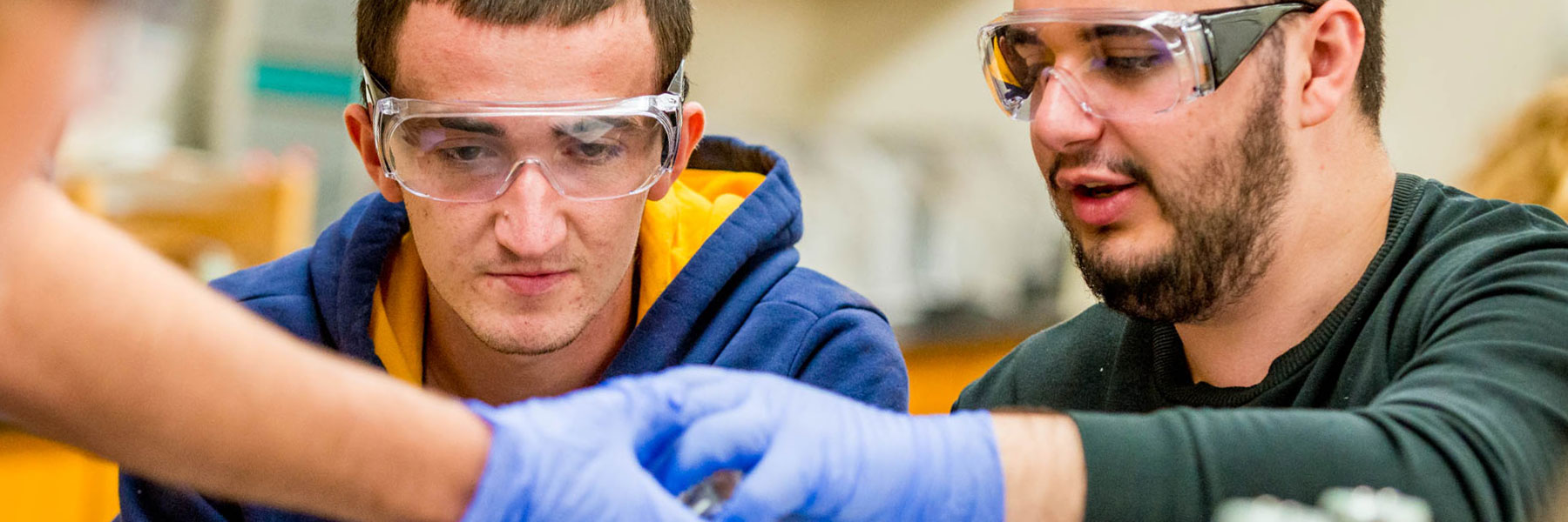 two male students with goggle and protective gloves handle objects in chemistry class