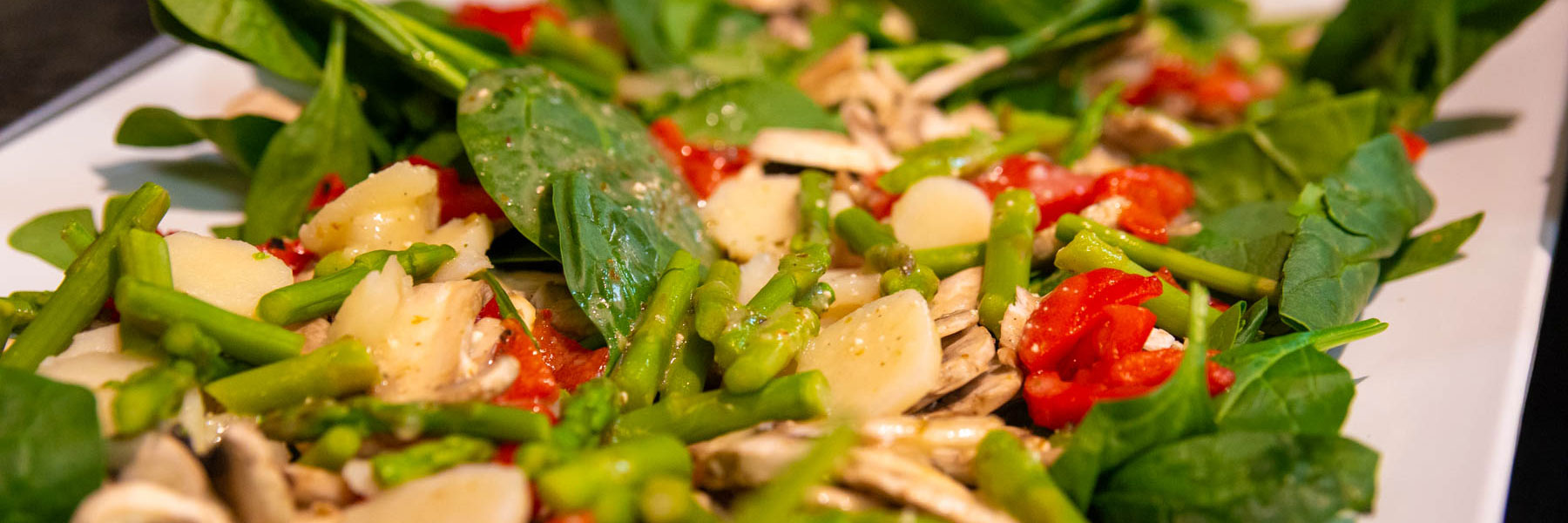 close up photo showing a spinach salad with water chestnuts, asparagus, tomatoes, and dressing