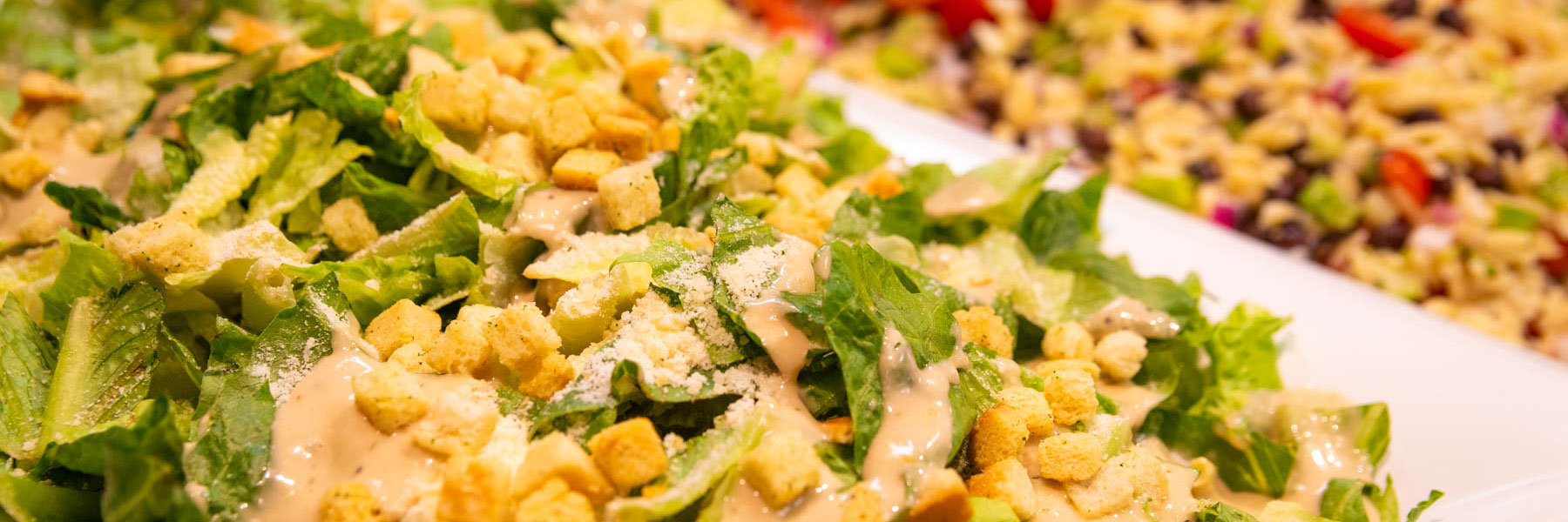 close up photo showing a lettuce salad with croutons and dressing