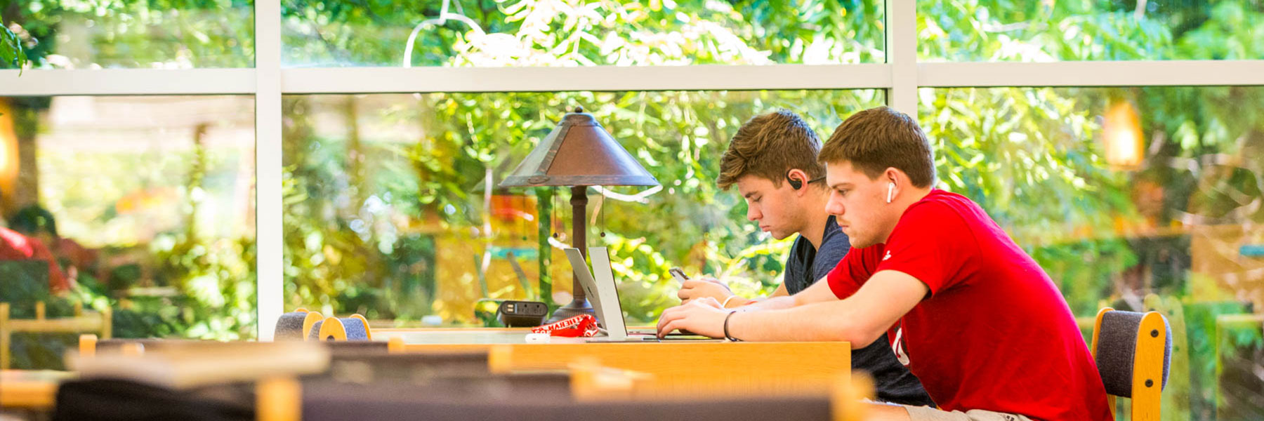 two male students seated at a desk look at their laptops while studying in memorial library
