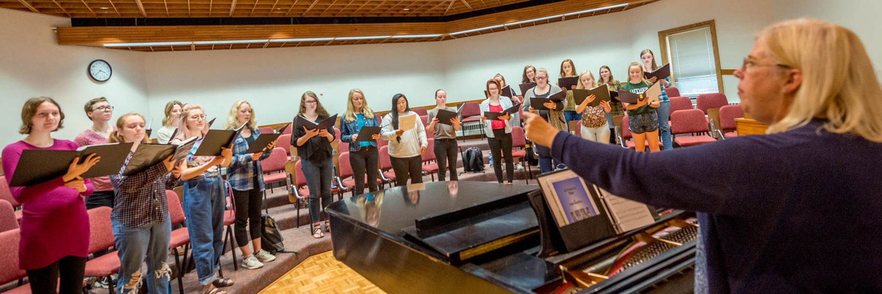 a room full of female singers look at their director as she conducts them in a choir rehearsal