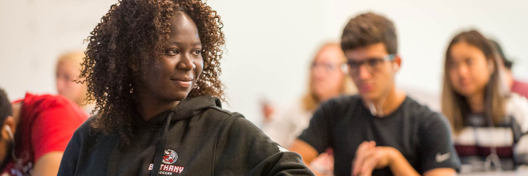 a female student smiles as she looks at another student in a classroom