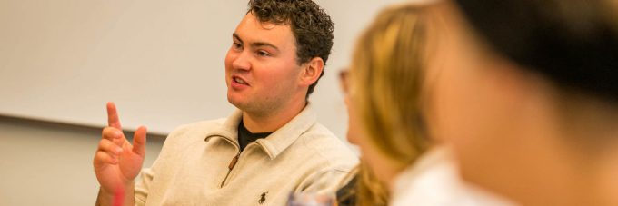 a male student talks and gestures with his hands during a classroom discussion