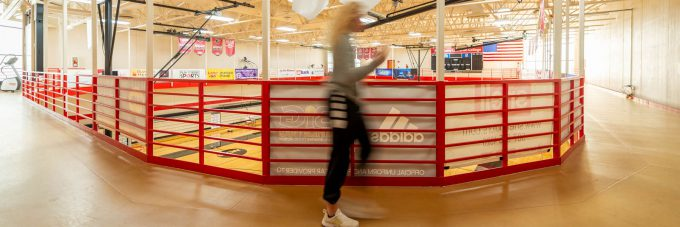 a female student is blurred in motion as she runs on a suspended track that runs along the wall of the sports and fitness center north gymnasium