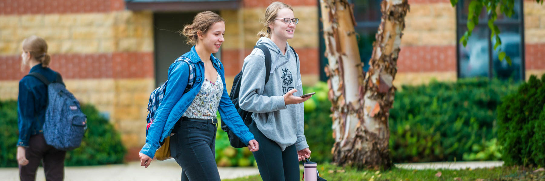 two female students talk outside while walking