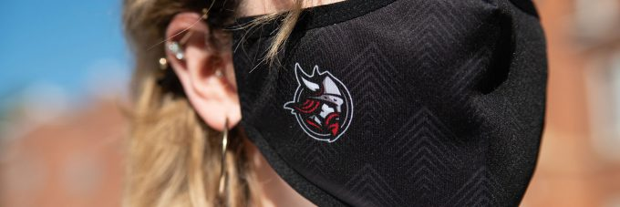 detail of viking logo on black mask worn by female outside