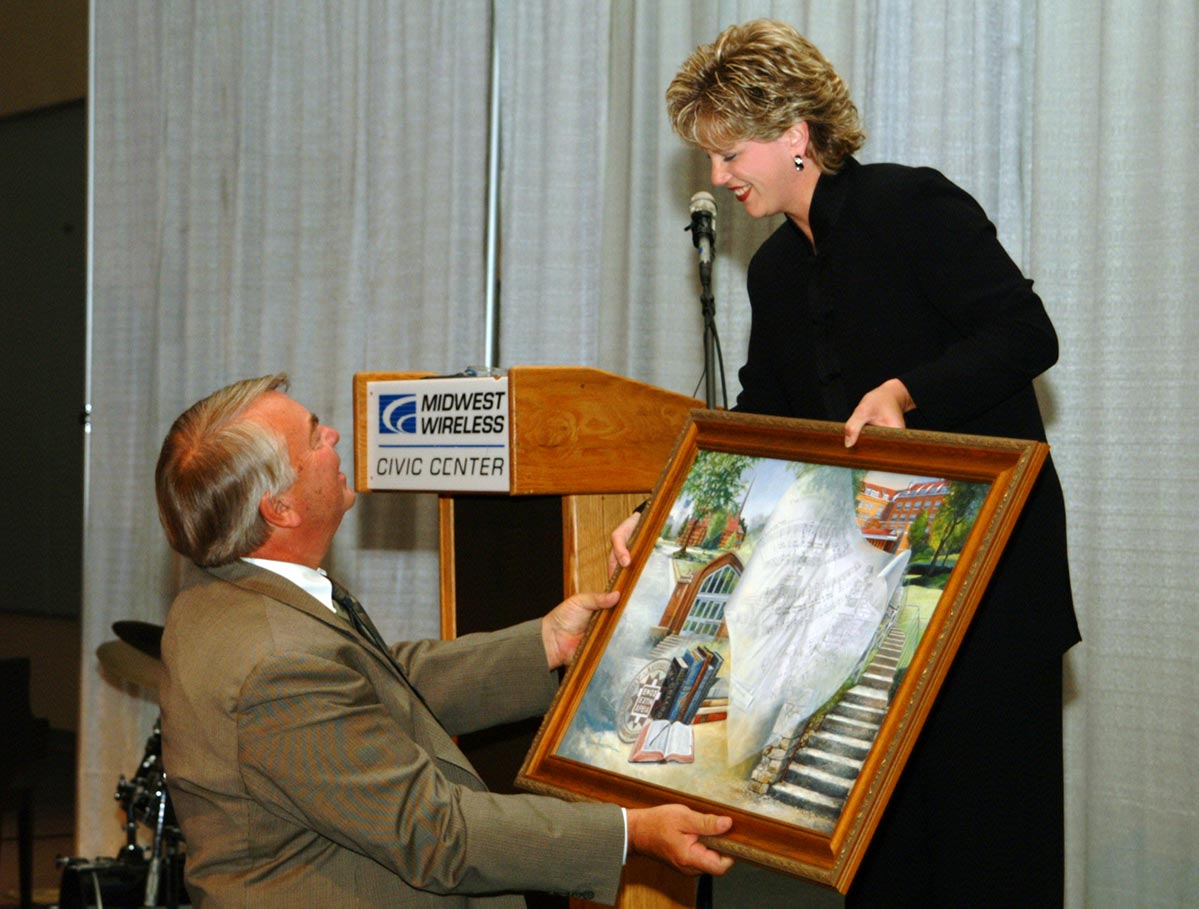 President Marvin Meyer receives a gift from Alumni Board President Kaye Anderson
