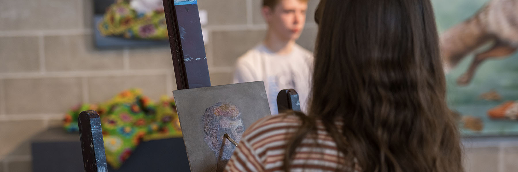 Photo of visiting artist painting portrait of male student in the gallery