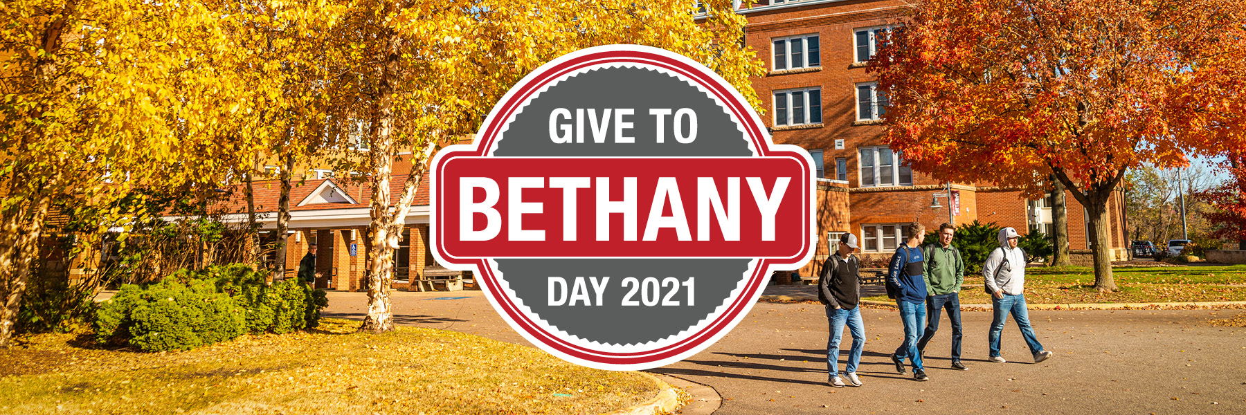 Give to Bethany Day 2021 text logo over photo of fall leaves and four male students walking, 2021