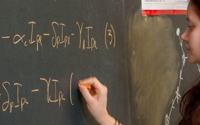 Student at chalk board writing out mathematic formulas.